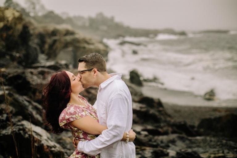 Engaged couple kissing on Marblehead Coast