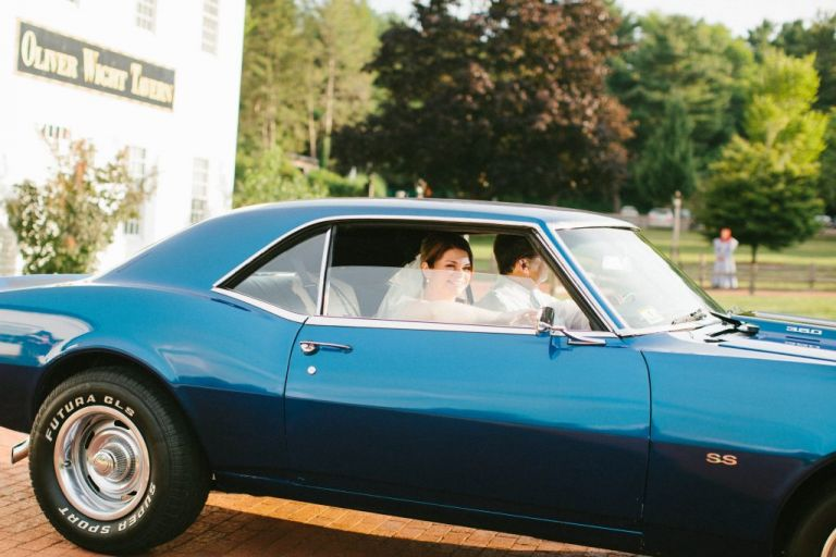 Bride arrives at her wedding in a classic blue mustang