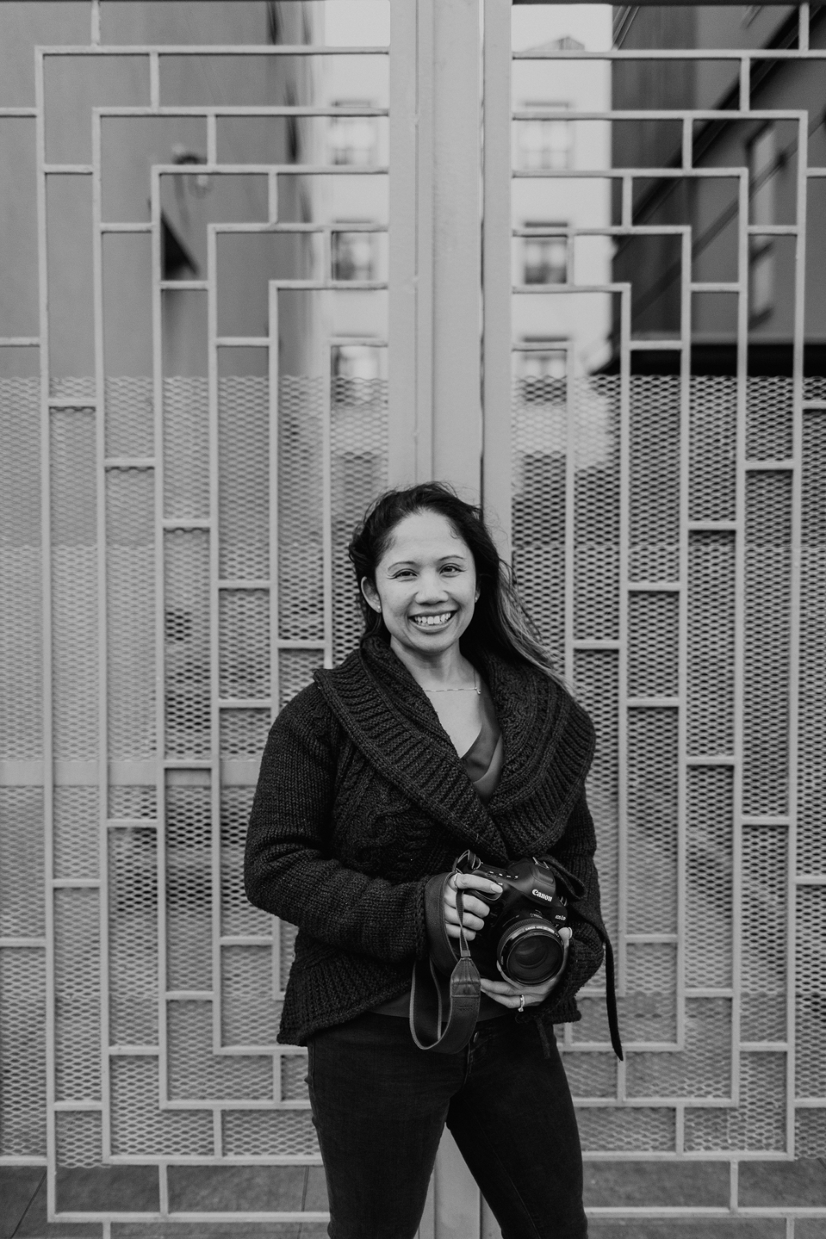 Black and white photo of Arlene D Marston in front of a gate with geometric patterns